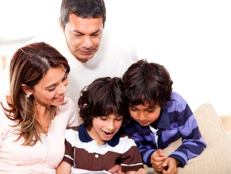 Happy family at home reading a book together