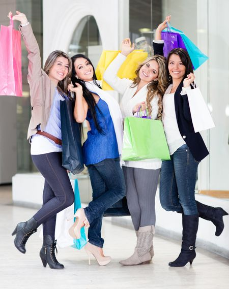 Happy shopping women with arms up at the mall