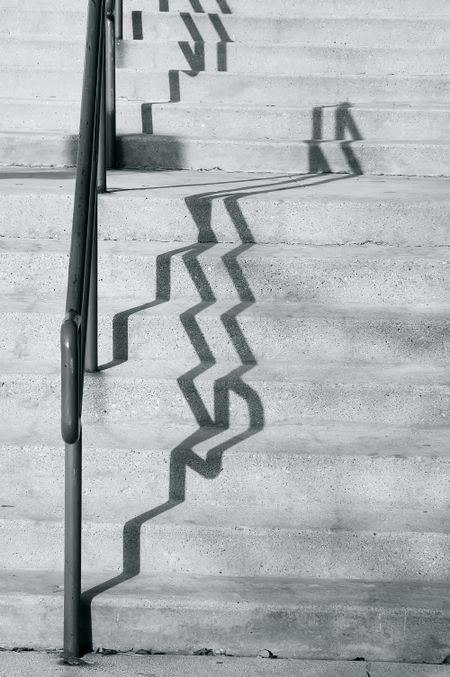 Shadows of handrail on concrete stairs