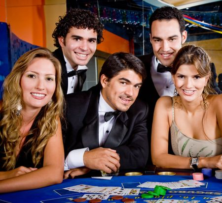 Group of people smiling playing roulette at the casino
