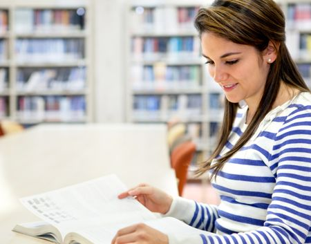 Woman studying at the library and reading a book