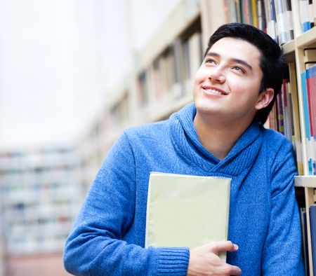 Thoughtful male student at the library holding a book