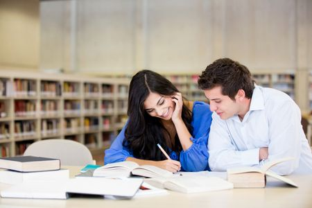 Happy young couple studying at the library