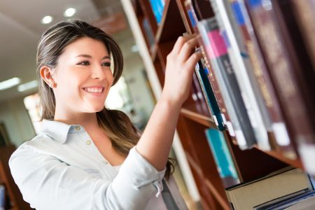 Female student at the library looking for a book