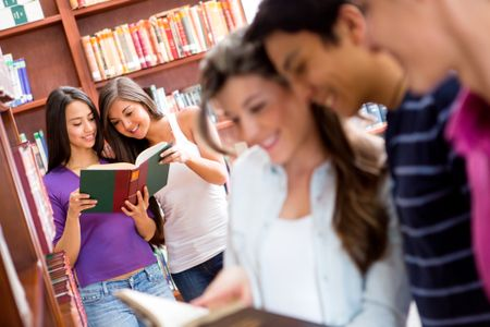 Group of students researching at the library and reading books