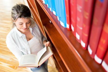 Female student at the library reading a book