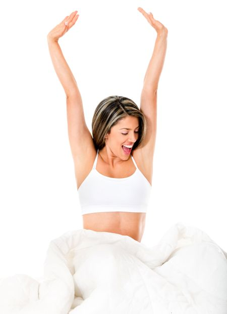 Beautiful happy woman in bed - isolated over a white background