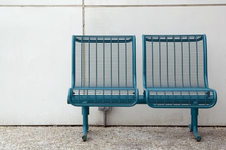 Pair of metal seats by white wall on college campus