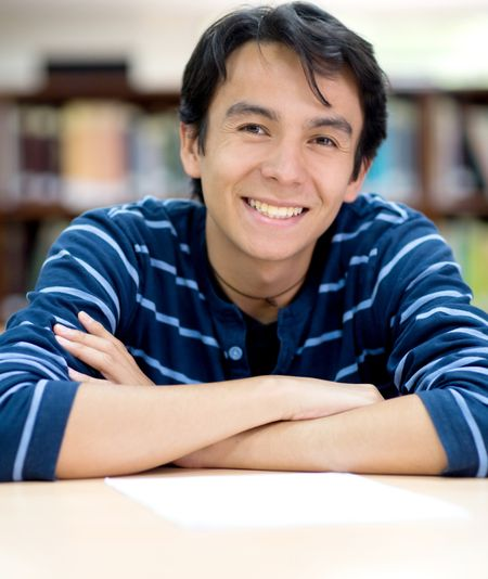 Happy male student smiling at the library