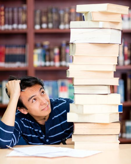 Overwhelmed male student with a pile of books