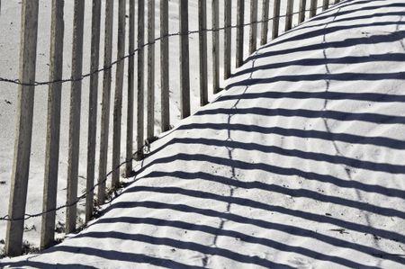 Beach fence and shadows on sand