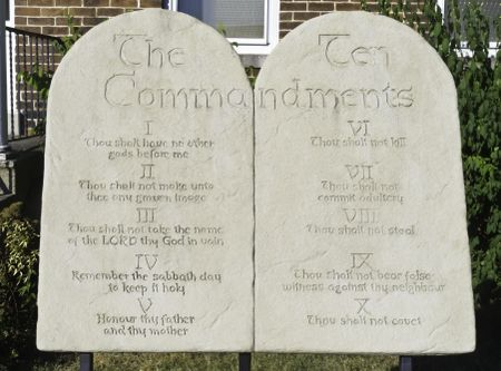 Two stone tablets engraved with the Ten Commandments in front of urban brick church