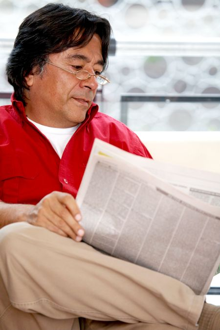 man reading the newspaper at his home
