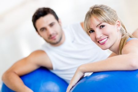 Attractive couple at the gym exercising with Pilates balls