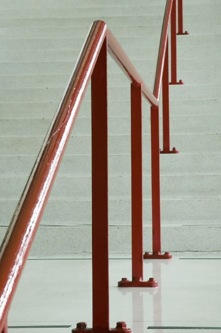 Red handrail along off-white staircase