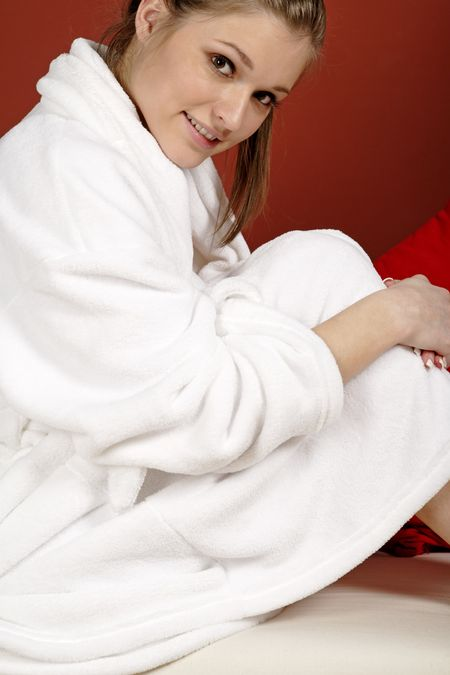 Young woman sat on her sofa at home wearing a white bath robe
