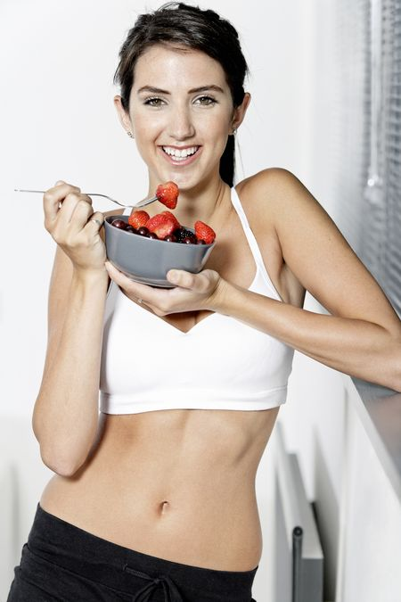 beautiful young woman in fitness clothes eating fresh fruit from a bowl at home
