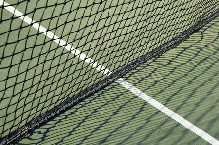 Net and shadows on outdoor tennis court