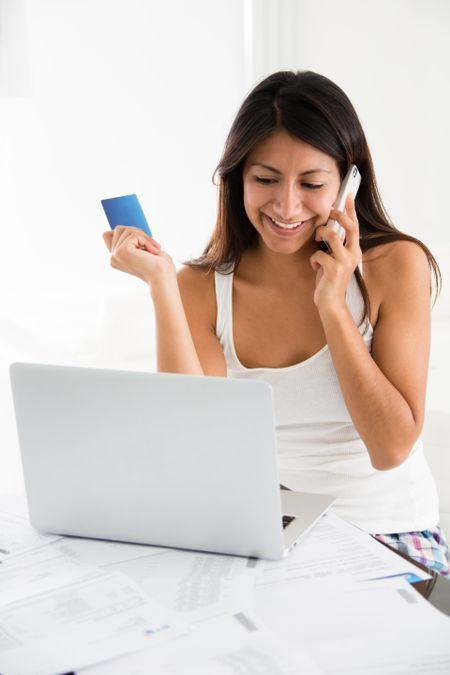Woman talking to the bank on the phone and buying online