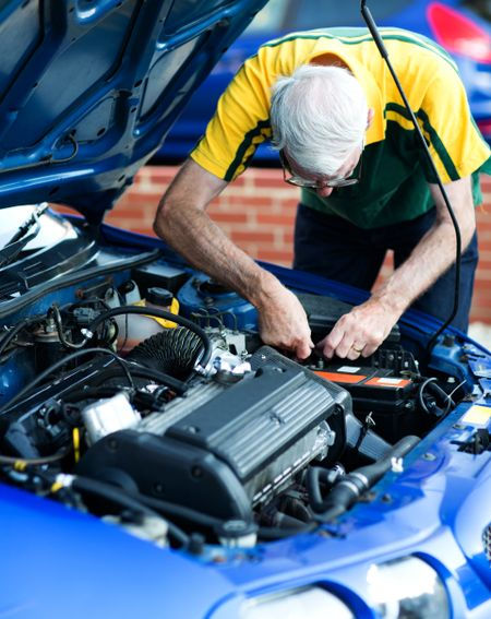 Casual man working on a car engine as a mechanic