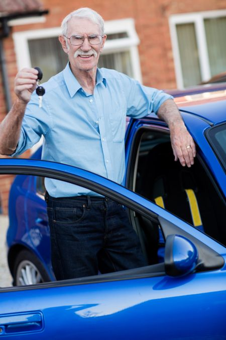Man holding the keys of his car and looking happy