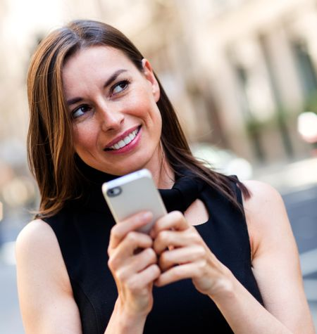 Woman replying a text message on her mobile phone