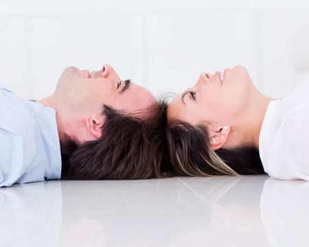 Couple lying on the floor looking up and smiling