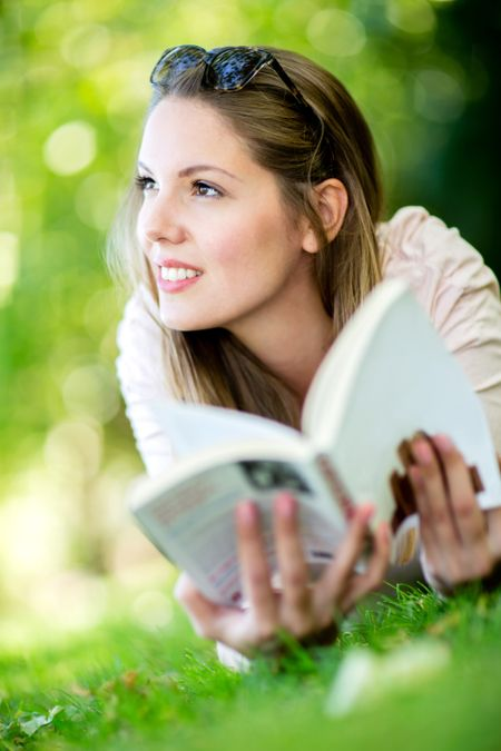 Thoughtful woman reading a book outdoors and smiling