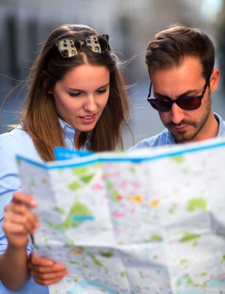 Lost tourists on their vacations looking at a map