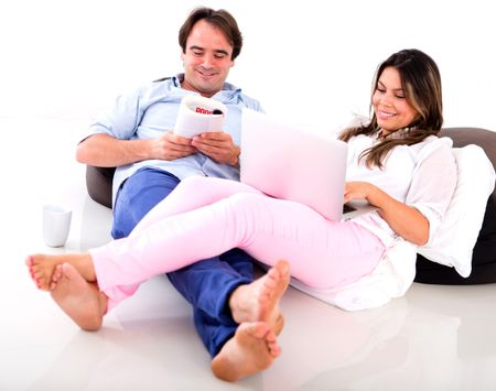 Couple relaxing at home reading and looking very happy