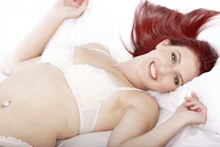 Attractive young woman lying on her bed in her underwear at home