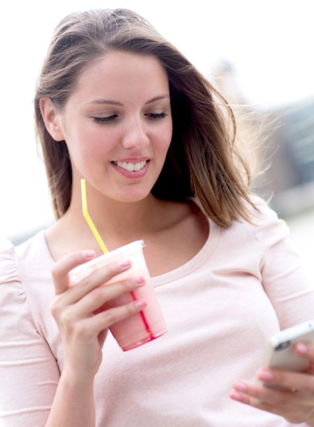 Woman enjoying a milkshake and texting on her phone
