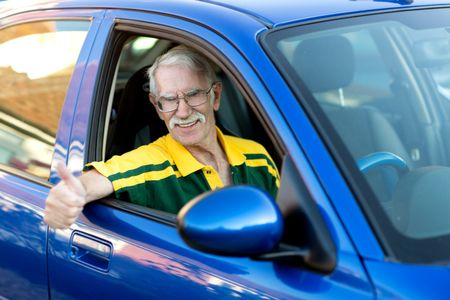 Senior man driving a car and looking very happy