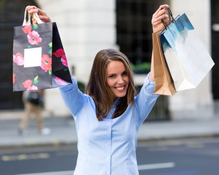 Happy female shopper with arms up and smiling