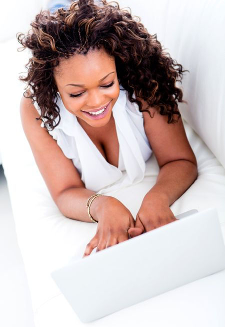 Happy woman working on a laptop computer from home