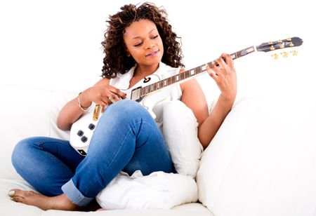 Beautiful woman playing guitar and relaxing at home