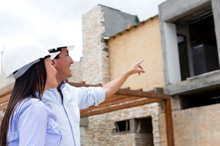 Engineers at a construction site pointing one house