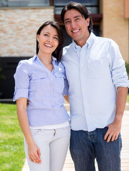 Happy casual couple standing outside their house