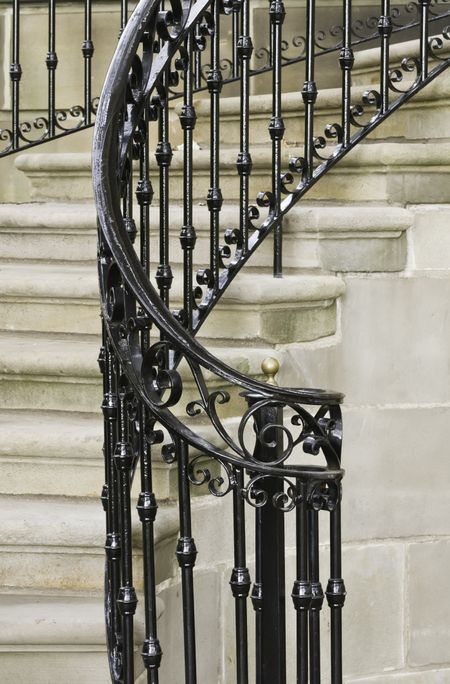 Vintage ironwork on winding staircase at front entrance to building