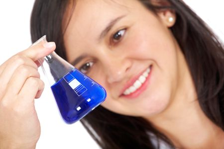 chemistry student smiling while looking at a test tube with blue liquid inside