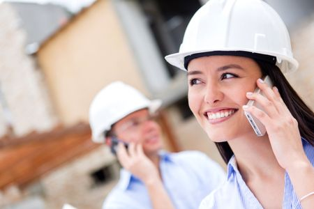Architects talking on the phone at a building site