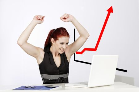 Professional young woman celebrating at work in her office, with a concept, graph displaying a great increase.