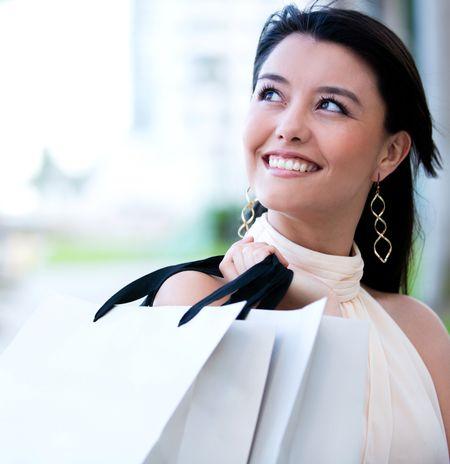 Beautiful female shopper holding shopping bags