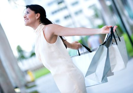 Excited shopping woman with arms up holding bags