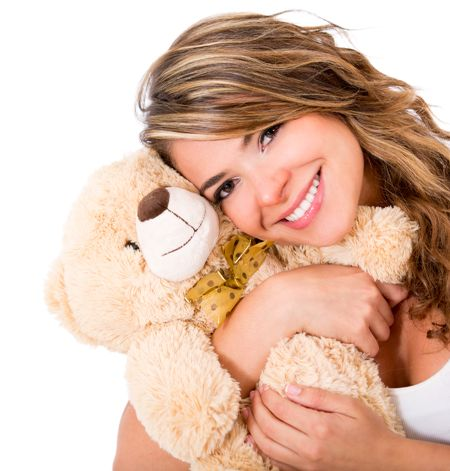 Cute woman holding a teddy bear - isolated over a white background