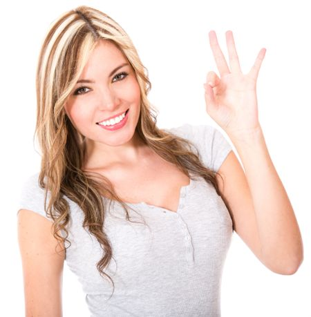 Woman giving her ok sign - isolated over a white background
