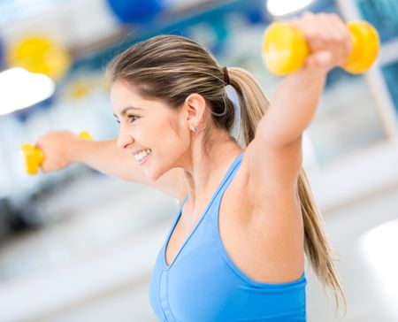 Fit woman lifting free weights at the gym