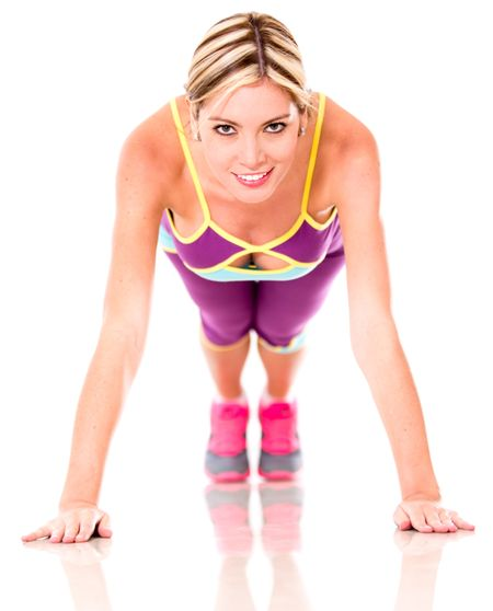 Fit woman doing push ups - isolated over a white background