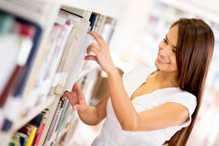 Female student looking for a book at the library