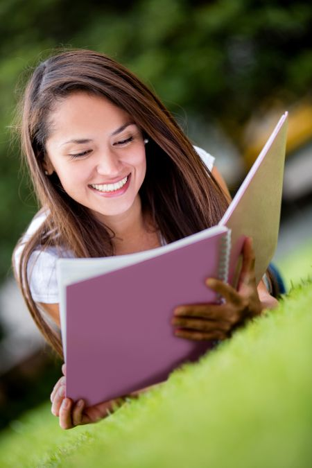 Female student studying outdoors looking very happy